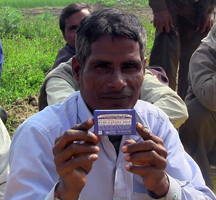 A peppermint farmer in India holds up one of the final products he supplies mint for
