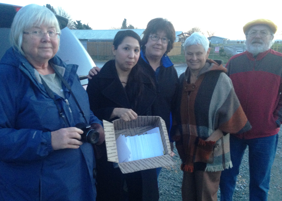 Representatives of the National Farmworker Ministry hold box of 750 postcards
