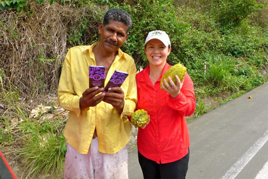 Equal Exchange Co-op farmer holds chocolate bars and cacao pods